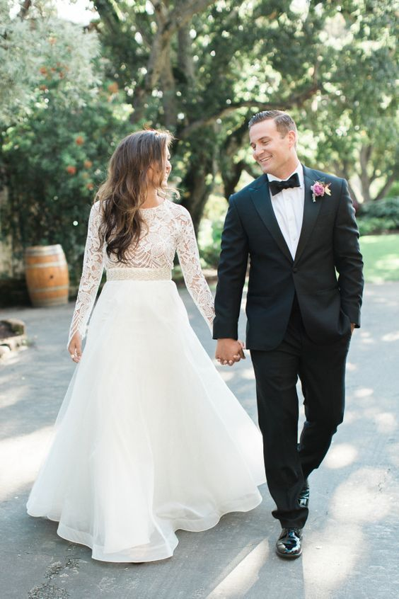a modern A-line wedding dress with a lace bodice with long sleeves and a layered tulle skirt