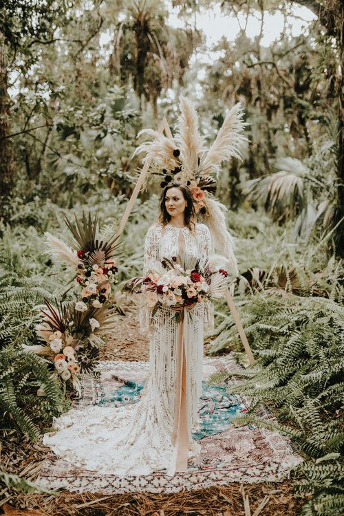 Dakota boho lace sheath wedding dress with long bell sleeves, a train, a cutout neckline and fringe