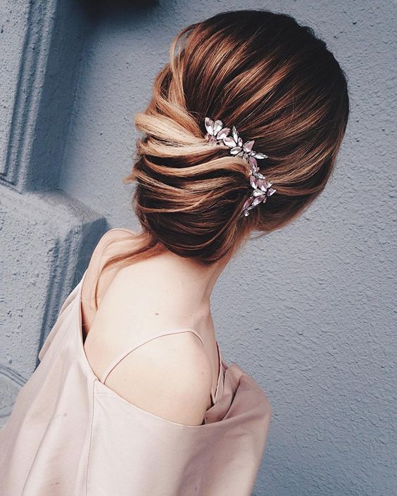 a beautiful low updo with side twists and a chic rhinestone hairpiece