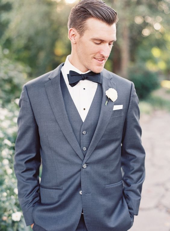a classic graphite grey three piece wedding suit with a black bow tie and a shirt with black buttons