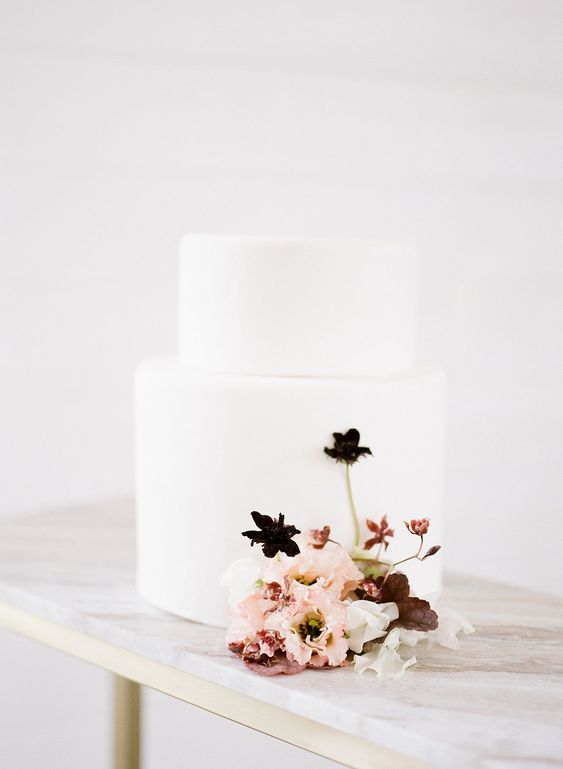 a minimalist wedding cake in white with some dark and blush blooms for a minimal wedding