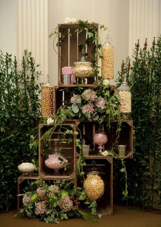a sweets table alternative built of crates, decorated with blooms and greenery and with candy jars inside