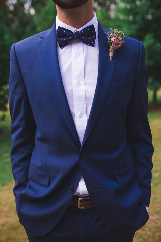 a bold blue suit with a white shirt, a polka dot bow tie and a brown belt for making a statement