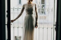 19 a chic fitting dress with a lace embellished bodice with long sleeves and a high neckline and a plain skirt