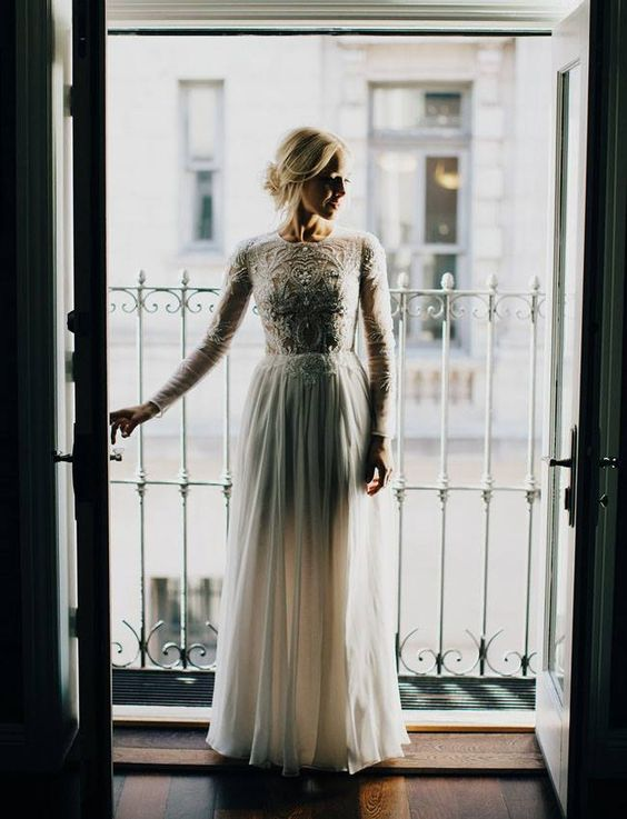 a chic fitting dress with a lace embellished bodice with long sleeves and a high neckline and a plain skirt
