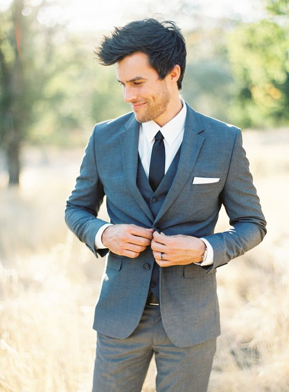 a grey three piece wedding suit, a white shirt, a black tie is a modern look with a classic touch