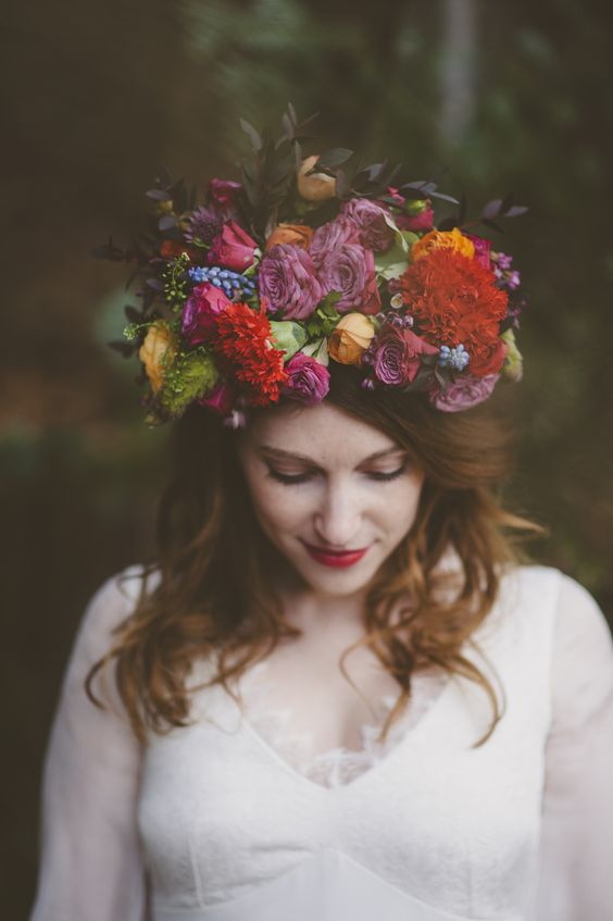 a lush oversized floral crown with all kinds and colors of blooms and some leaves for a summer bride