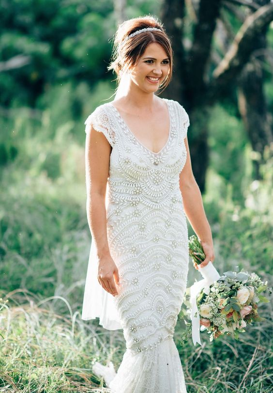 a mermaid embellished wedding dress with a V-neckline, cap sleeves and a small train