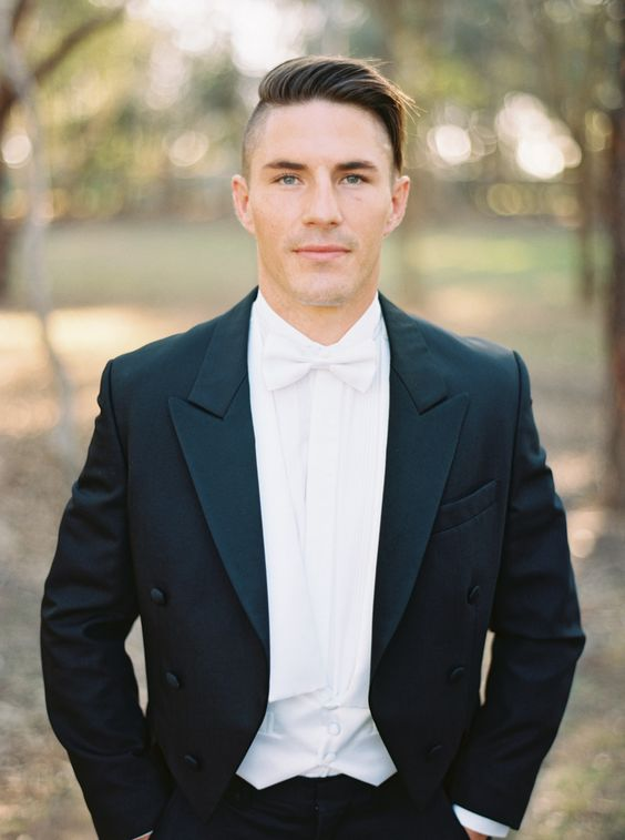a vintage-inspired look with a black tuxedo, a white vest and shirt plus a white bow tie