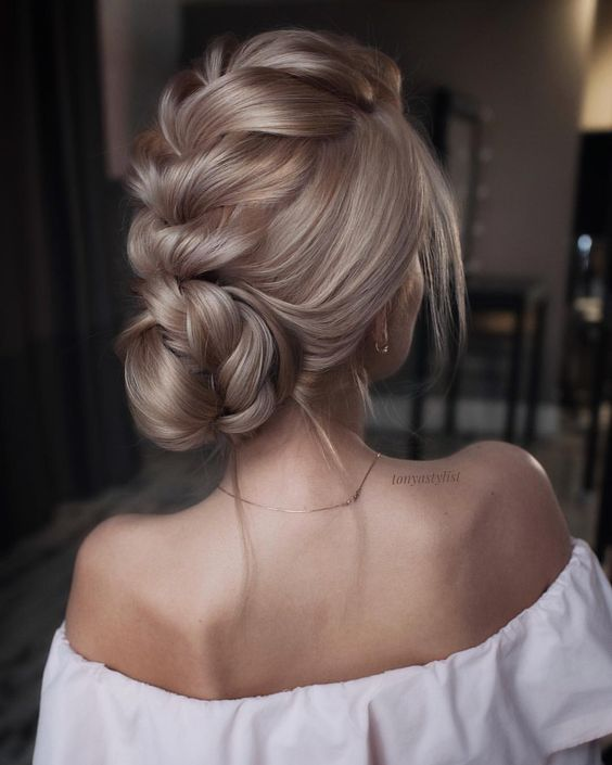 a voluminous braided updo with a large central braid and a low bun plus some locks