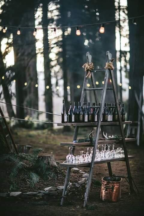 a woodland wedding bar made of a ladder and shelves and decorated with moss and antlers