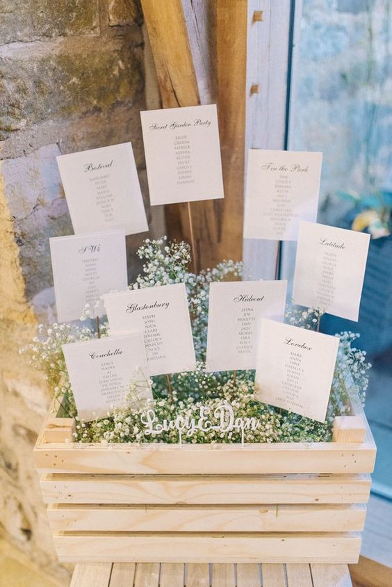 display your seating chart in a crate filled with baby's breath and with a seating plan