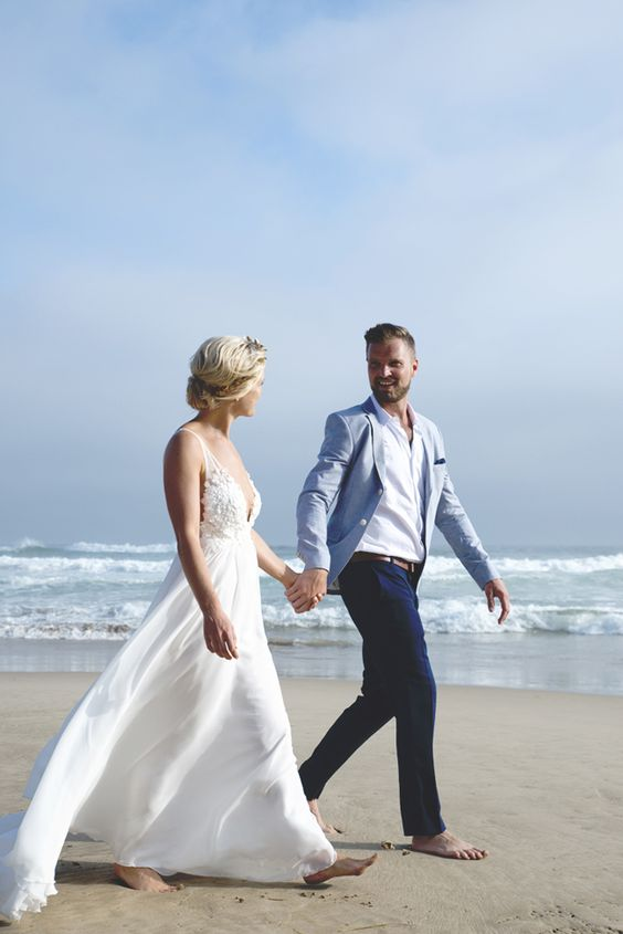 navy pants, a white shirt and a light blue jacket, no tie for an oceanside wedding