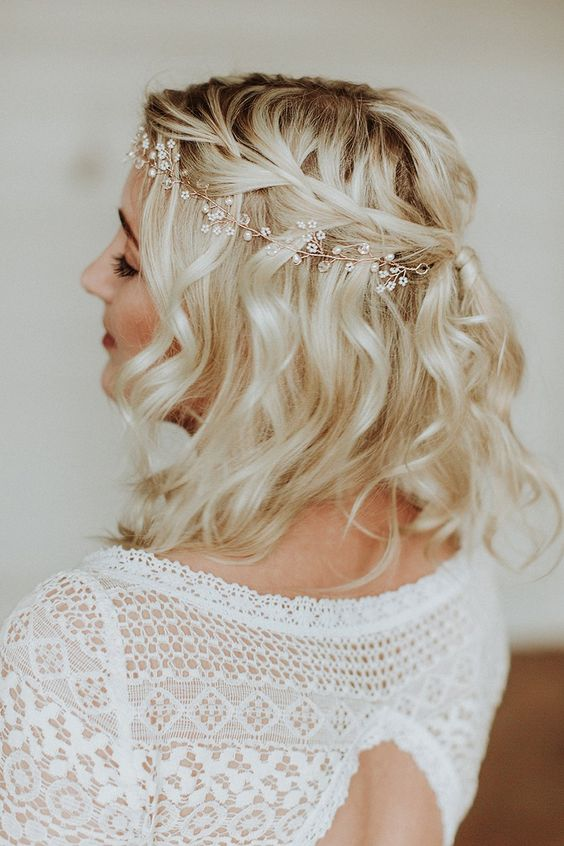 a half updo with a halo braid and waves accented with a hair vine for a boho bride