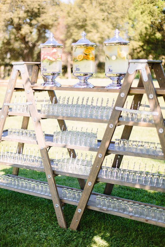 a large wedding drink bar made of a couple of ladders and drinks in sheer tanks