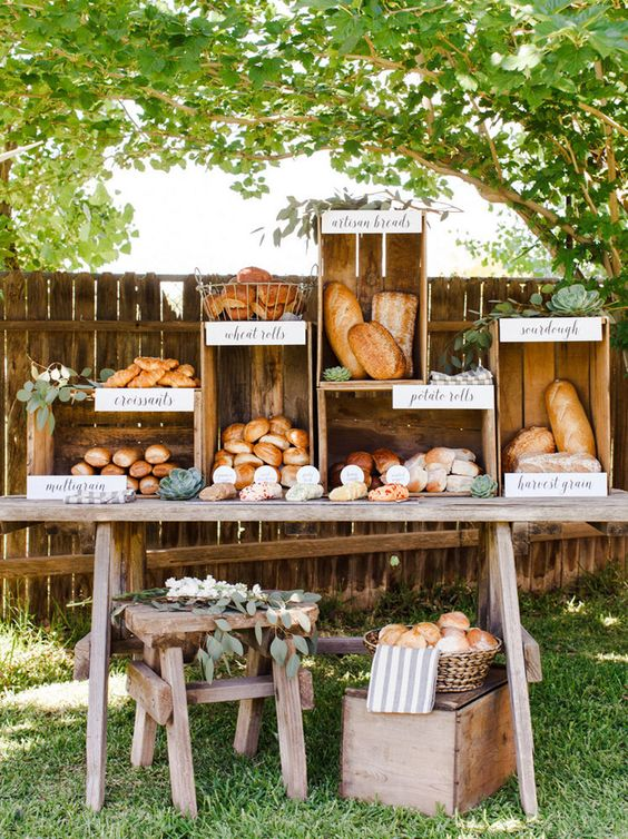 a bread and pastry station made of a rustic table and some crates placed on each other for a farmhouse wedding
