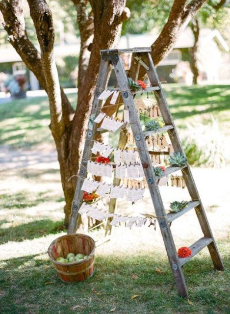 a ladder seating plan with escort cards and succulents for a rustic wedding