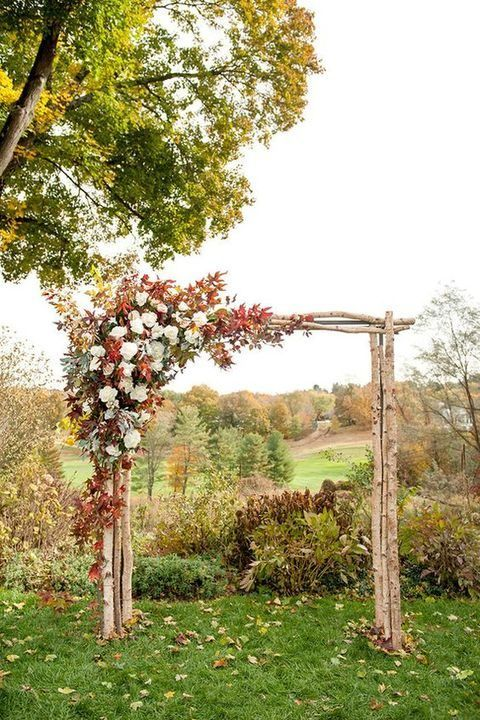 a rustic fall wedidng arch of wood branches and lush leaves and white blooms for decor