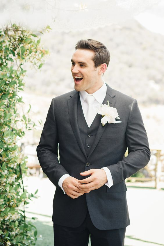 a graphite grey three-piece wedding suit with a white shirt, tie and a white floral boutonniere for a formal look