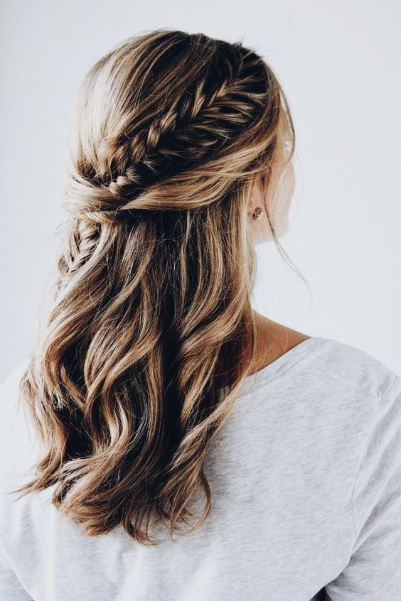 a half updo with a side braid and waves looks very soft and romantic