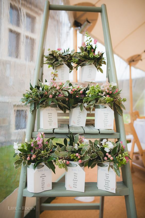 a ladder seating plan with floral combos in tin cans and seating plan attached to them