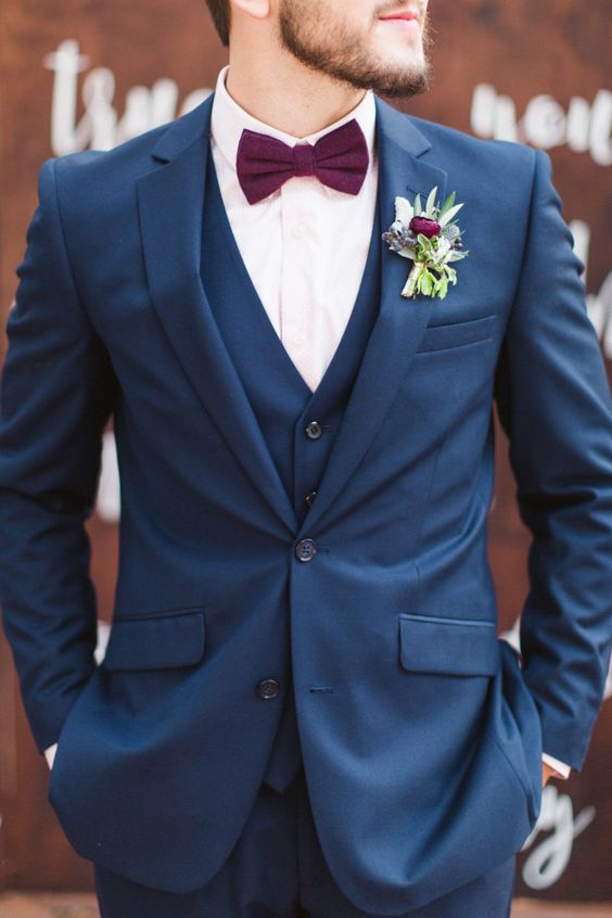 a navy three piece suit with a plum colored bow tie and a cool boutonniere