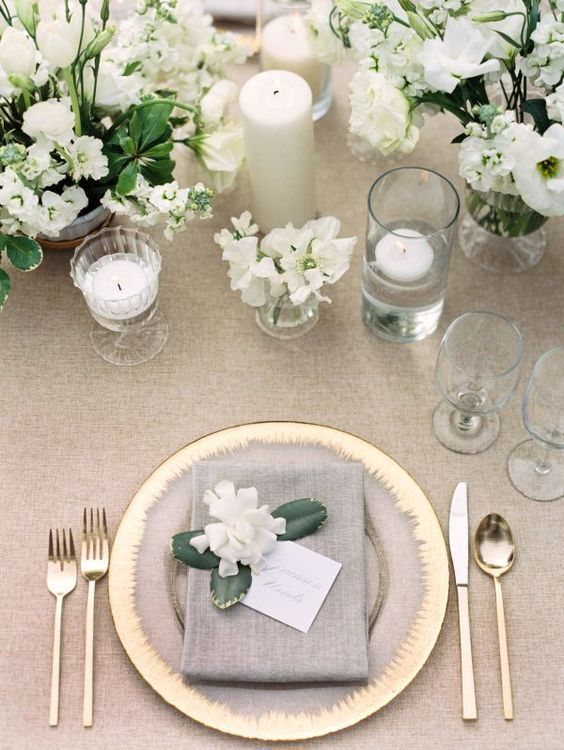 a chic neutral tablescape with taupe and gold plus white candles and blooms