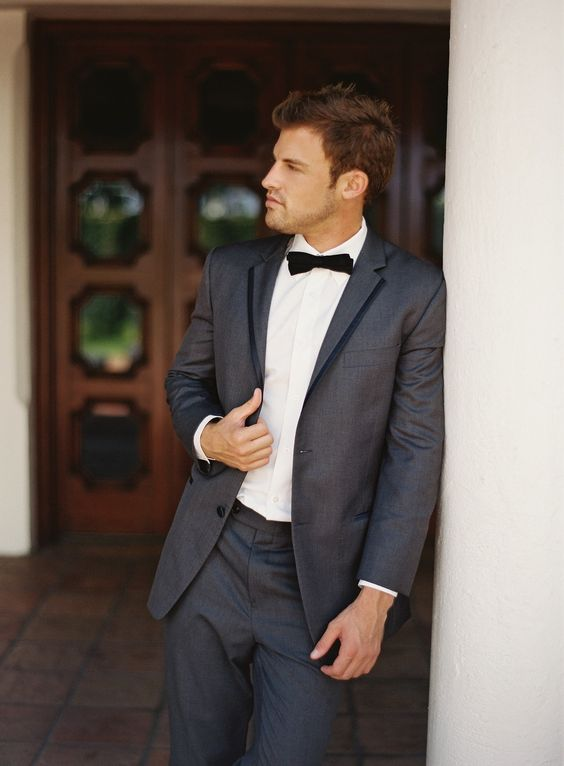 a graphite grey tuxedo with black rim lapels and a black bow tie is a fresh take on a traditional black one