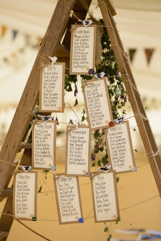 a ladder with a seating chart hanging on strings and lush greenery on it