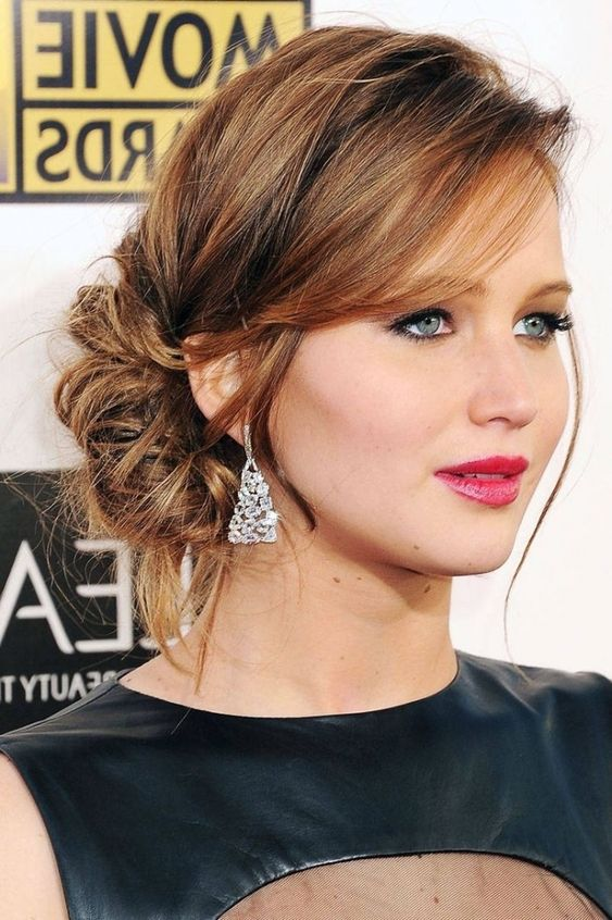 a messy side low bun with bangs and a side fringe for an effotlessly chic look