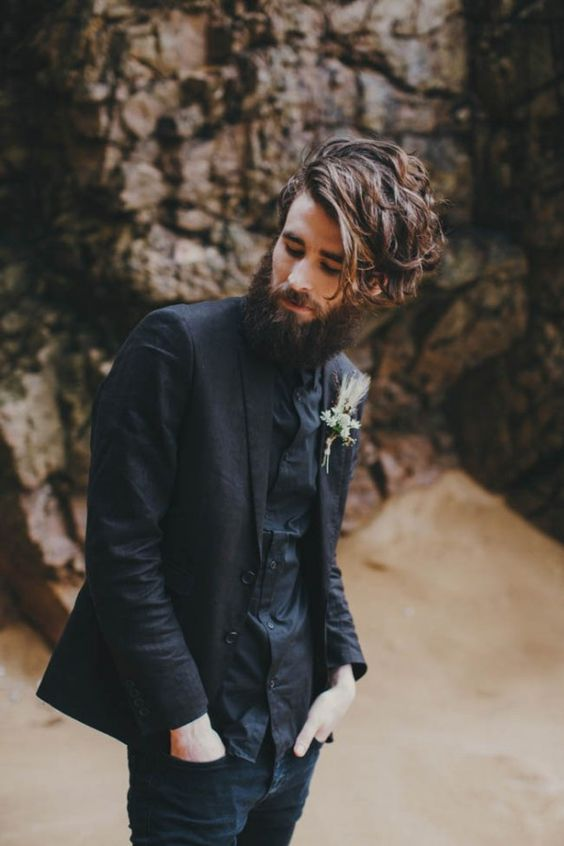 a relaxed total black look with a shirt, a jacket, jeans and a boutonniere for a boho feel
