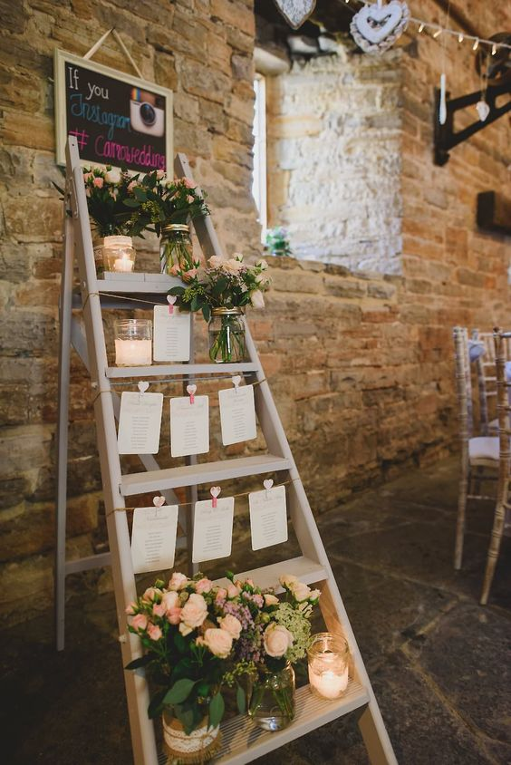 a seating plan made of a ladder and some sheets of paper attached to it plus blush florals in jars