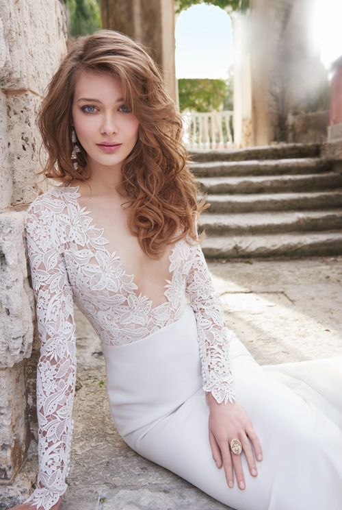 a stunning wedding dress with long sleeves and a lace bodice with a plunging neckline, a plain skirt