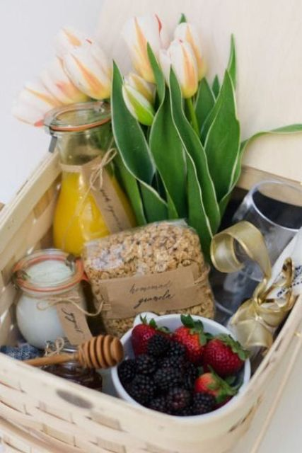 a wedding welcome bag with fruits, juices, flowers, honey packed into a crate