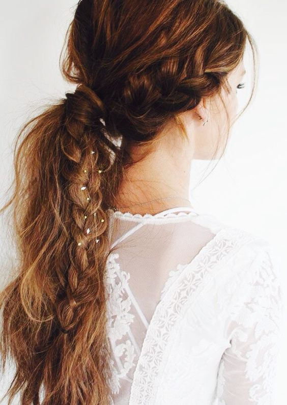 a messy textural ponytail with a bump and a side braid with tin flowers in for a boho bride