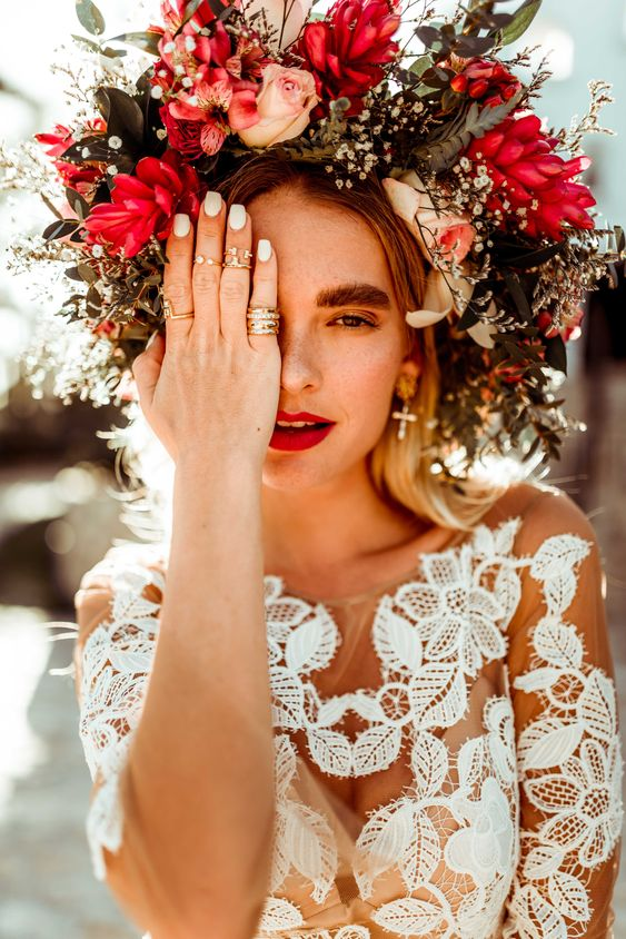 an oversized floral crown with blush, red and white blooms and textural greenery for a fall boho bride