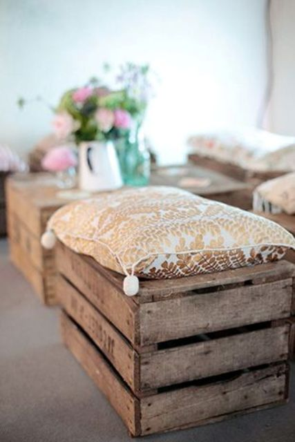crates with soft pillows on them can be used as rustic wedding seats