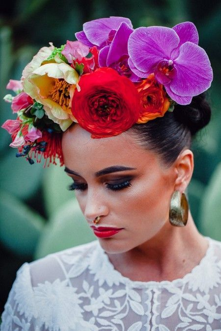 Frida Kahlo inspired bridal look accented with an oversized floral crown with fuchsia and red blooms