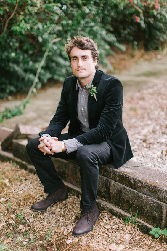 a rustic groom's look with a grey shirt, a black velvet jacket, black pants and brown boots