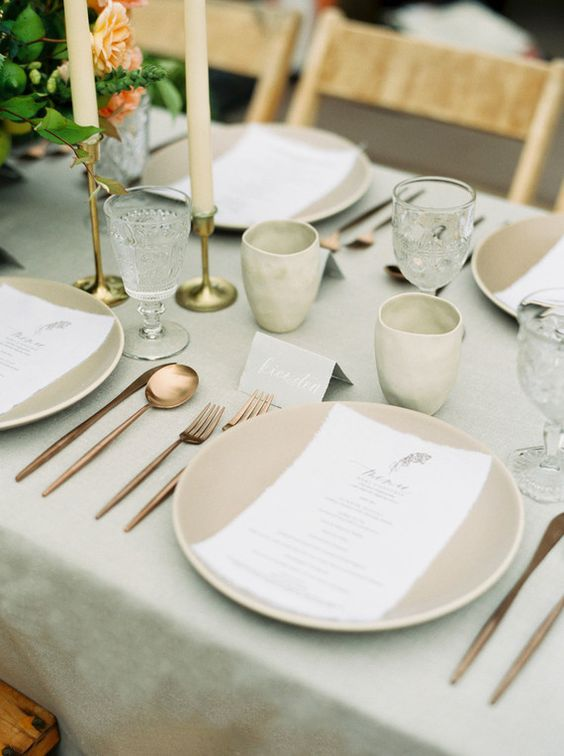 a taupe and grey table setting with cutlery and bright blooms for a fall wedding