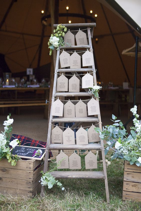 a wedding seating plan of a ladder with seating plan hanging on strings and lush greenery and flowers