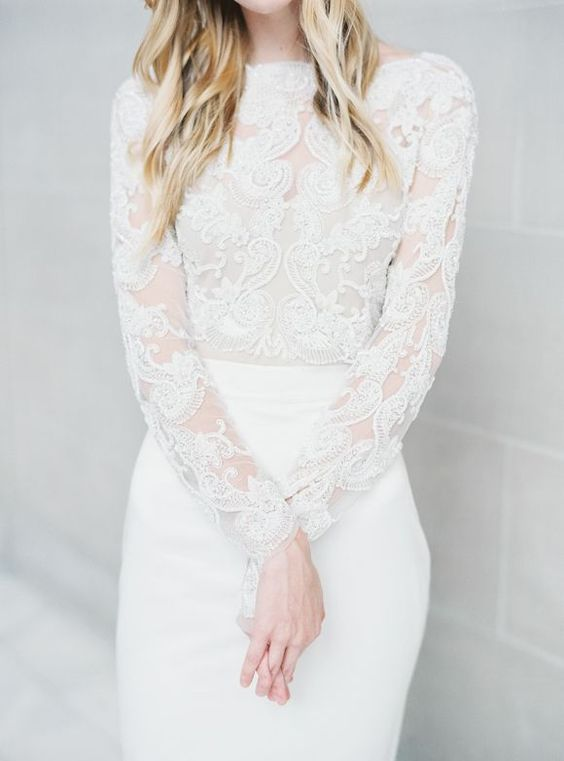 an ethereal wedding dress with a lace bodice with long sleeves, a high neckline and a sleek skirt