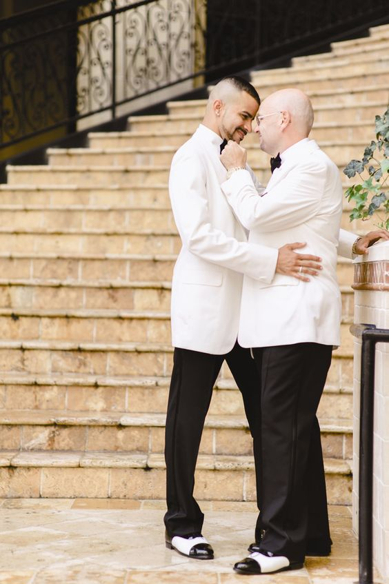 both grooms wearing white tuxedos and vintage-inspired black and white shoes