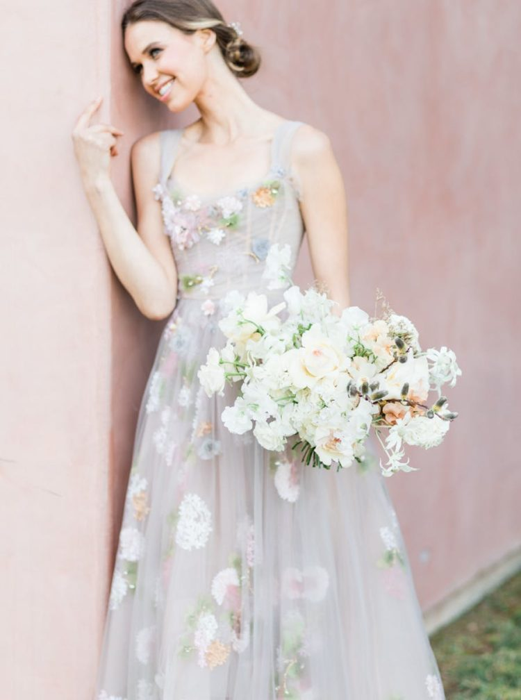 The bride was wearing a fantastic pastel floral wedding gown by Marchesa, a low updo with a headpiece