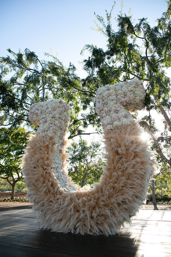 The wedding backdrop was a giant horseshoe of pampas grass and white and pink blooms on top