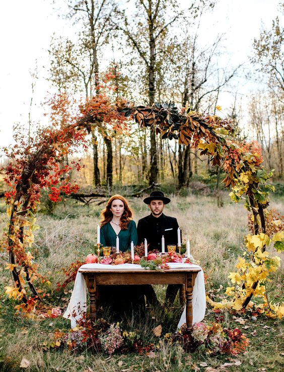 a circular fall woodland wedding arch with fall leaves, herbs and some bold blooms