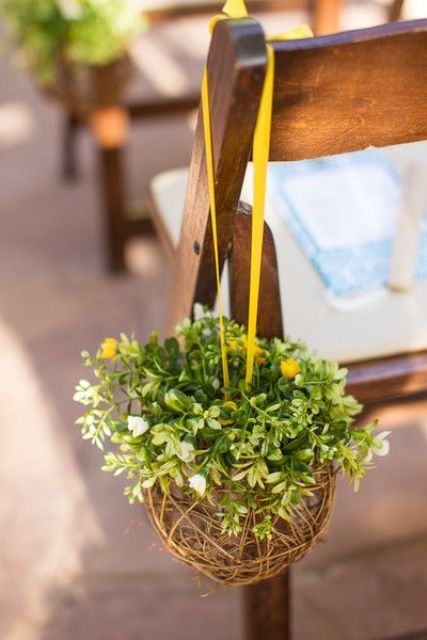 a cute topiary of wicker, greenery and some yellow blooms on a yellow ribbon is a creative fall idea