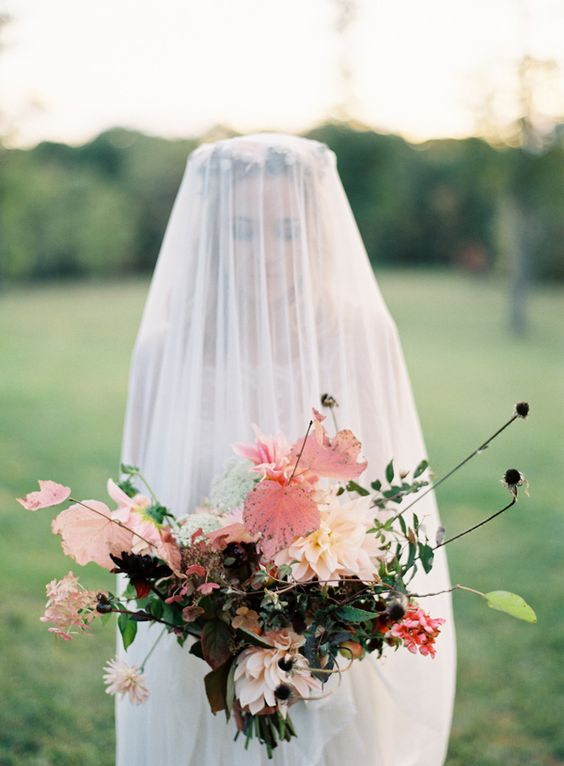 a decadent fall wedding bouquet done in black, blush and pink shades and with a catchy shape