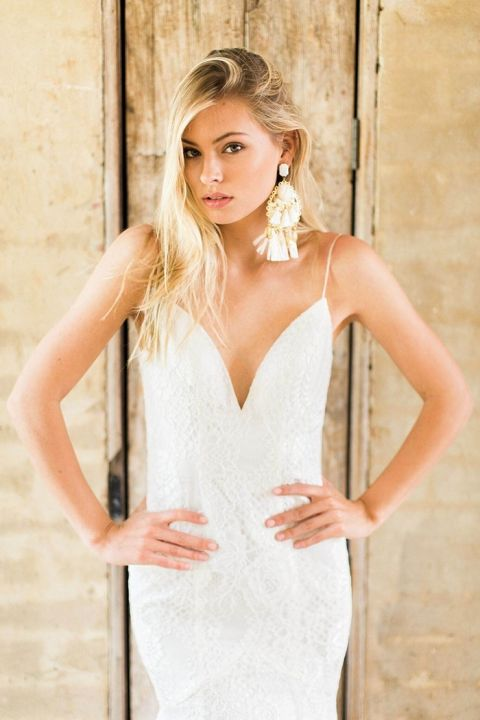 a glam and romantic bridal look with a lace sheath dress and oversized tassel earrings