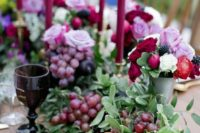 02 lush table decor of a foliage table runner dotted with grapes, plums and pomegranates plus jewel-toned candles